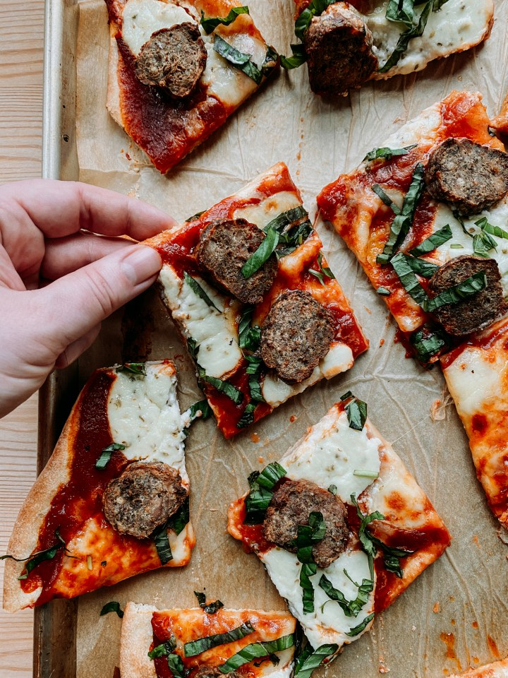 A hand grabbing a slice of meatball and ricotta pizza off of a baking sheet