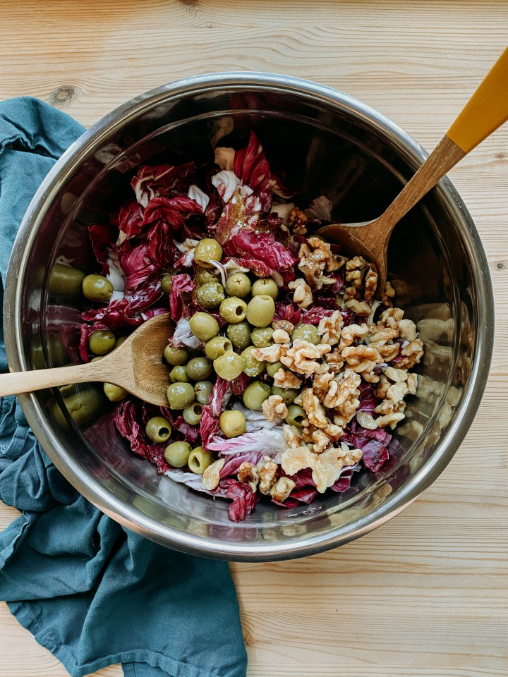 a large metal bowl containing radicchio leaves, vinaigrette, green olives, and candies walnuts resting on a dark teal towel on a wooden surface