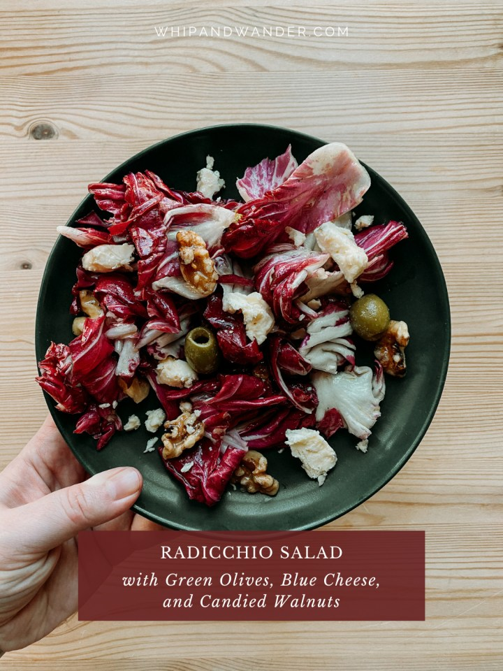 a hand holding a dark green salad plate with radicchio salad, blue cheese, candies walnuts, and castelvetrano green olives