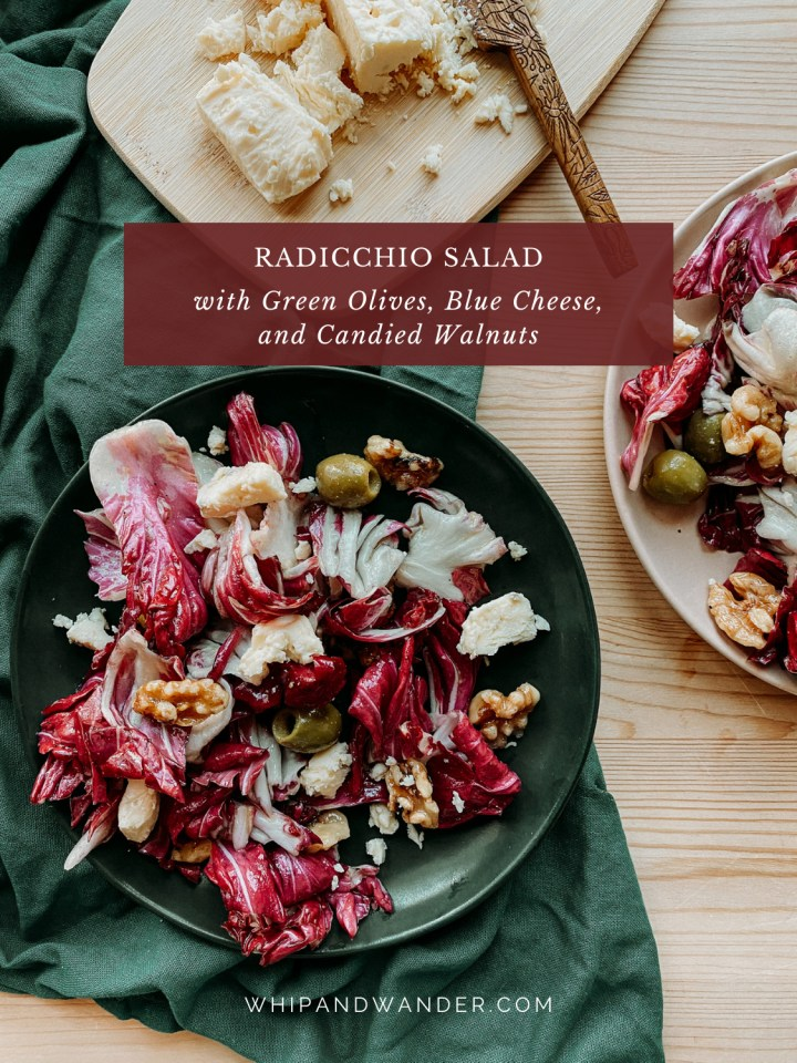 two plates covered in Radicchio Salad with Green Olives, Blue Cheese, and Candied Walnuts on a dark green towel on a wooden surface with a small wooden tray covered in gorgonzola cheese crumbles