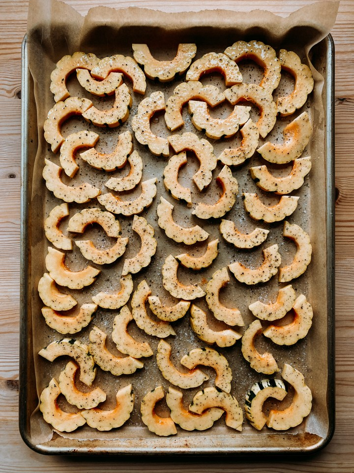 delicata squash that has beens slice dinto half moons resting on a parchment lines baking sheet before being baked