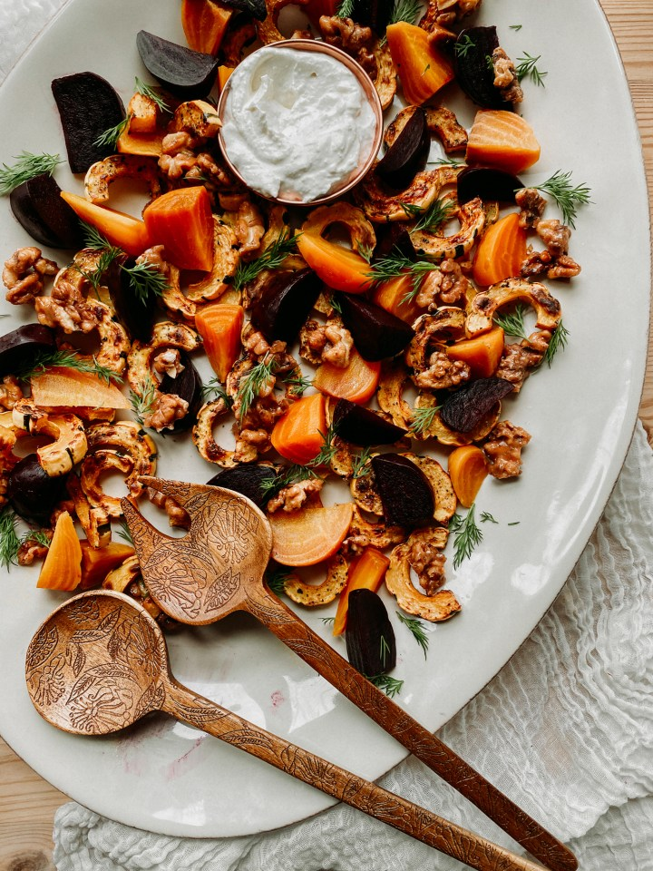 wooden serving utensils resting on a white platter of roasted beets, squash, walnuts, and a dish of horseradish cream