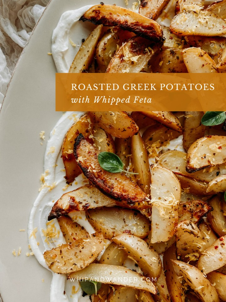 roasted greek potato wedges and fresh herbs and lemon zest resting on top of whipped yogurt and feta on a white dish