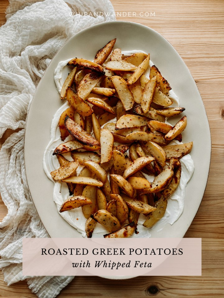 Roasted greek potatoes and whipped feta on top of a large white oval platter on a white fabric cloth on a wooden surface