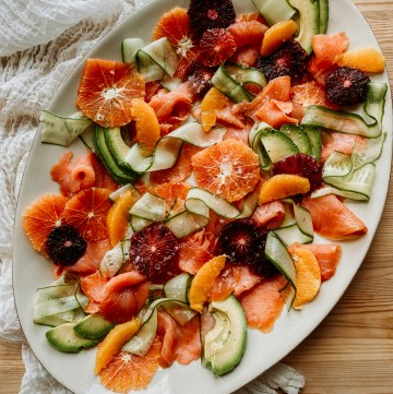Smoked Salmon and Citrus Salad with Cucumber and Avocado on a large white platter resting ona. neutral colored cloth on a wooden surface