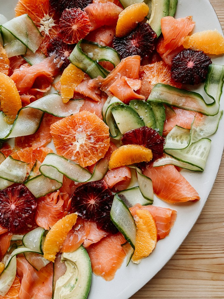 a white dish that contains a citrus and smoked salmon salad with cucumber and avocado