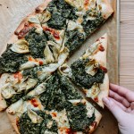 A hand grabbing a slice of Spinach Artichoke Pizza off of a parchment line baking sheet resting on a wooden surface