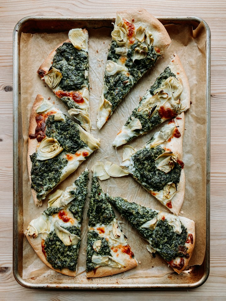 a spinach artichoke pizza that has been cut into 8 slices on a baking sheet