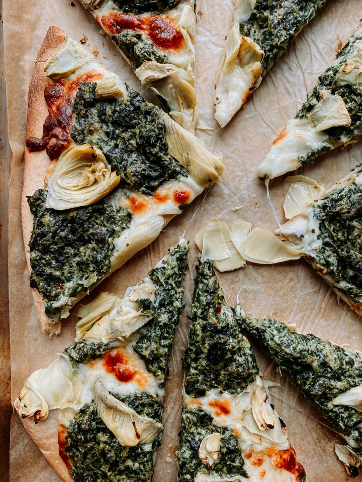 spinach artichoke pizza that has been cut into uneven slices resting on a parchment lined baking sheet