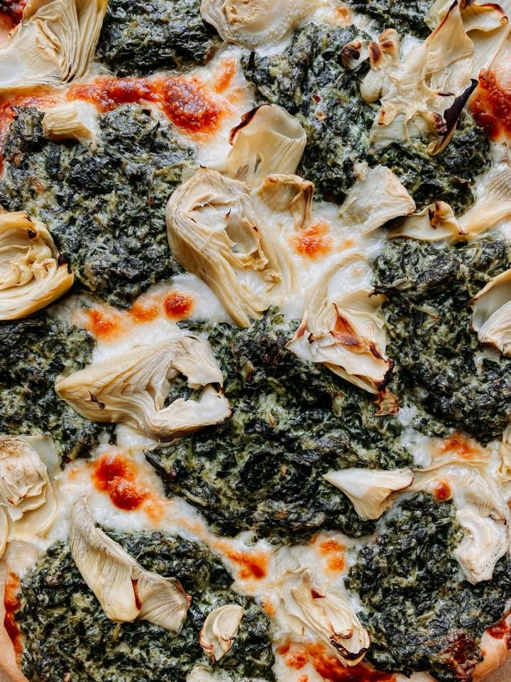 closeup of artichoke hearts, mozzarella, and creamy parmesan spinach dip on a pizza