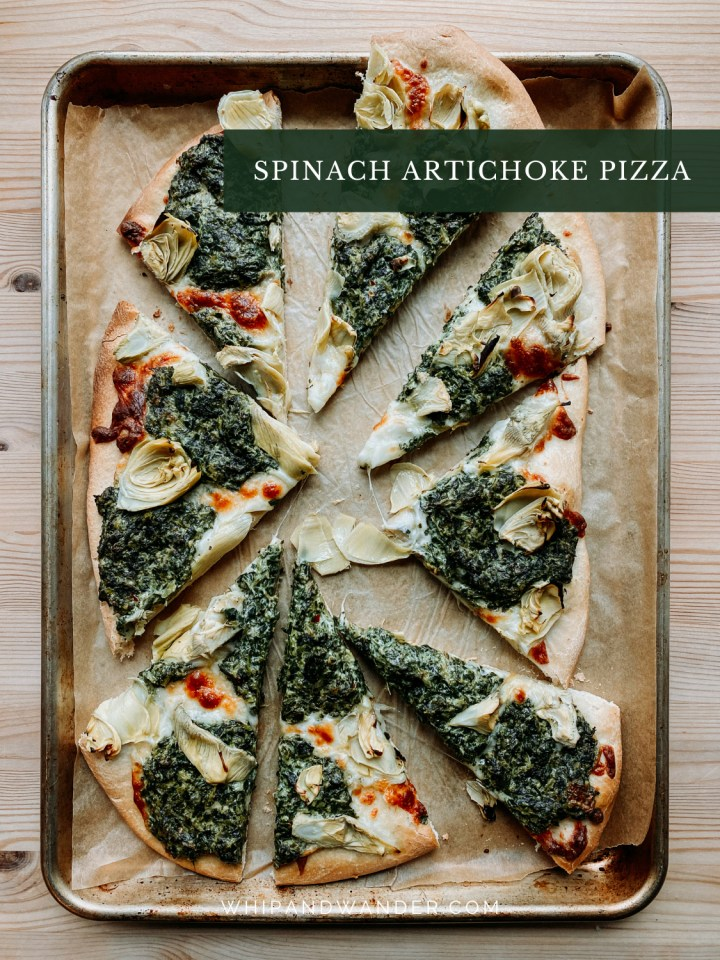 a parchment lined aluminum baking sheet covered with slices of spinach artichoke pizza