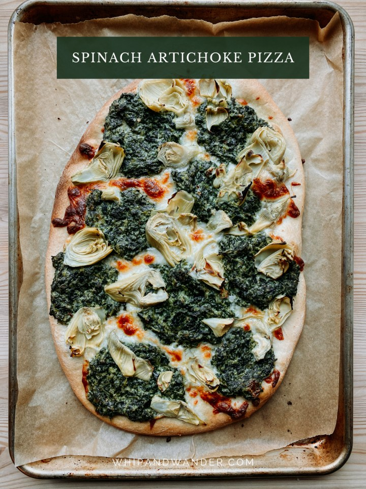 a whole, uncut pizza covered in artichoke hearts, spinach dip, and mozzarella cheese