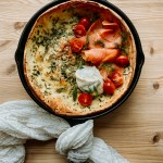 A Savory Buttermilk Herb Dutch Baby in a cast iron skillet topped with smoked salmon, tomato, and mascarpone resting on a wooden surface