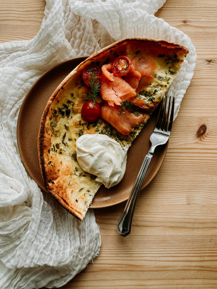 a brown plate with half of a Savory Buttermilk Herb Dutch Baby, smoked salmon, mascarpone, herbs, and tomatoes resting in top of a white cloth on a wooden table