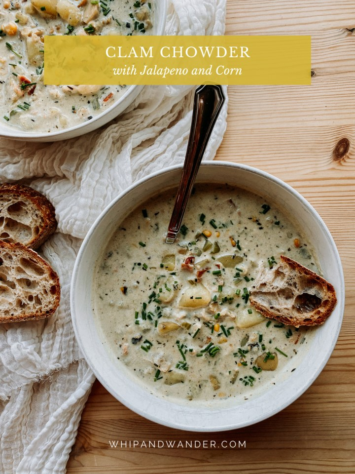 a spoon and a piece of bread resting in a dish of Clam Chowder with Jalapenos and Corn on a wooden table