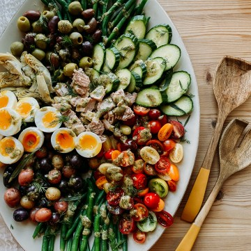 Tuna Salad Nicoise on a large white platter sitting on a wooden surface with salaf serving utensils resting to the right of the platter