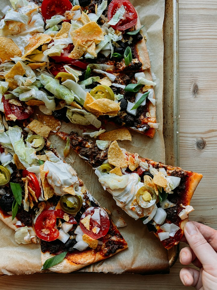 a hand grabbing a slice of Taco Pizza off of a baking sheet