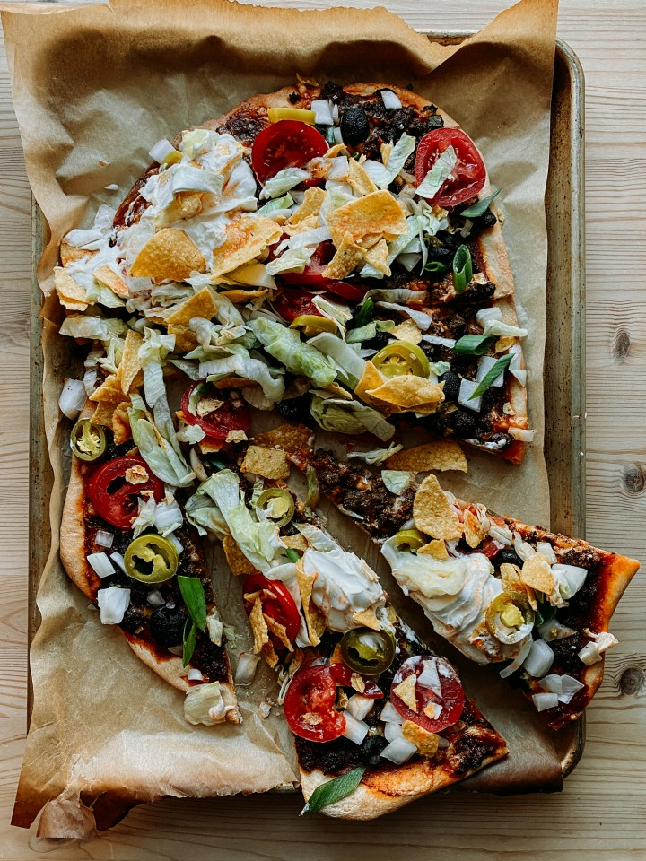 a Taco Pizza topped with lettuce, tomato, jalapenos, sou cream, and other taco toppings resting on a baking sheet