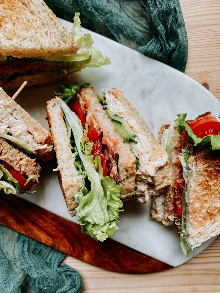 crab club sandwiches cut in half on a cutting board