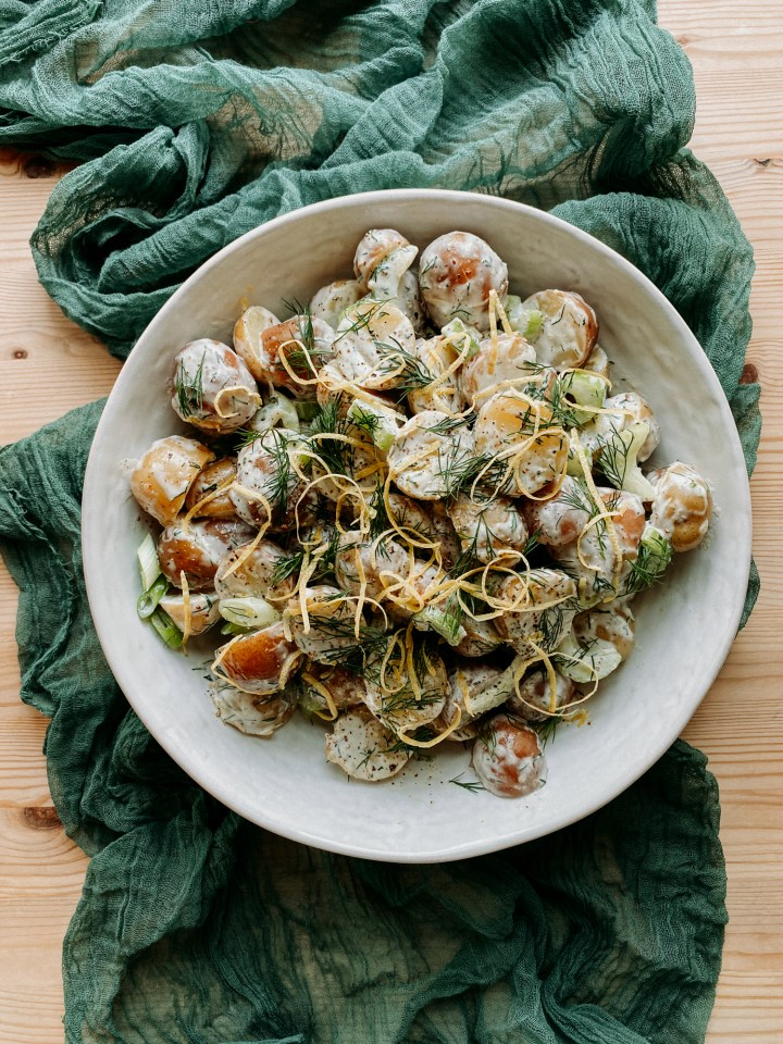 Creamy Dijon Dill Potato Salad in a white dish on top of a green cloth on a wooden table