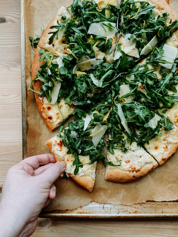 a hand grabbing a slice of white pizza bianca off of a bakers half sheet