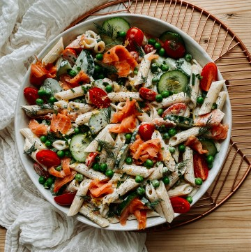 Penne pasta with tomatoes, cucumbers, smoked salmon, and herbs in a white bowl on a brass tray with a white cloth