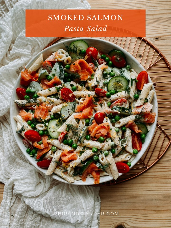 a large white serving bowl filled with penne pasta, smoked salmon, herbs, peas, tomatoes, and cucumbers