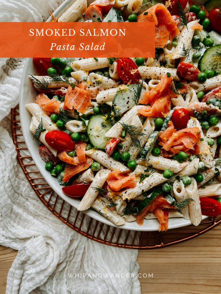 pasta salad with smoked salmon in a large white bowl over a white cloth lined wooden surface