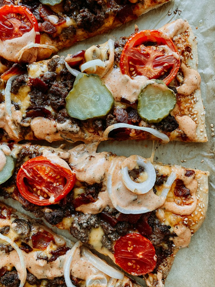 slices of tomato, olives, and pickle on top of a Bacon Cheeseburger Pizza