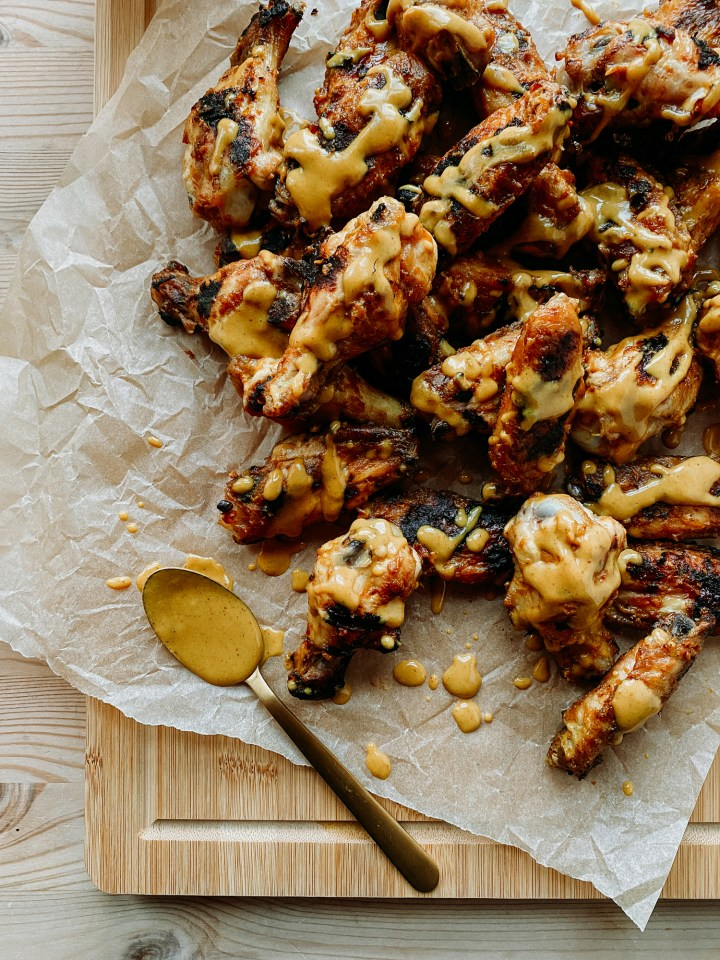 Grilled Chicken Wings with Carolina Gold Mustard BBQ Sauce on a parchment lined cutting board with a gold spoonful of sauce