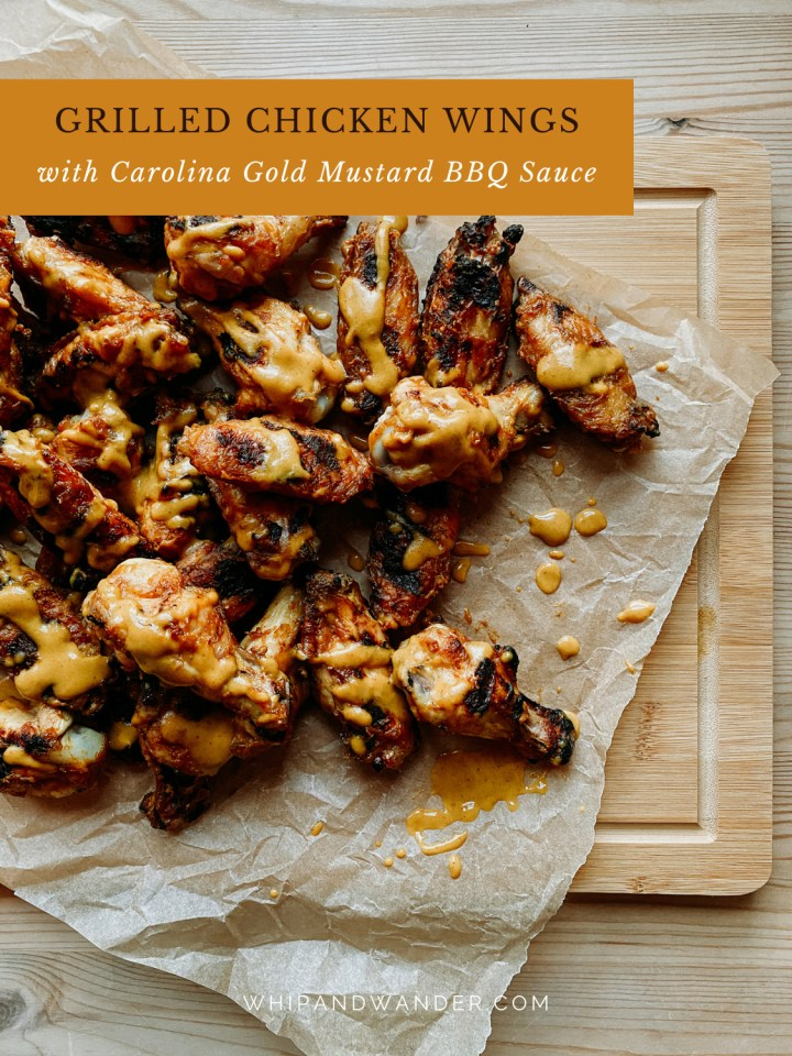 chicken wings in gold sauce on a wooden board