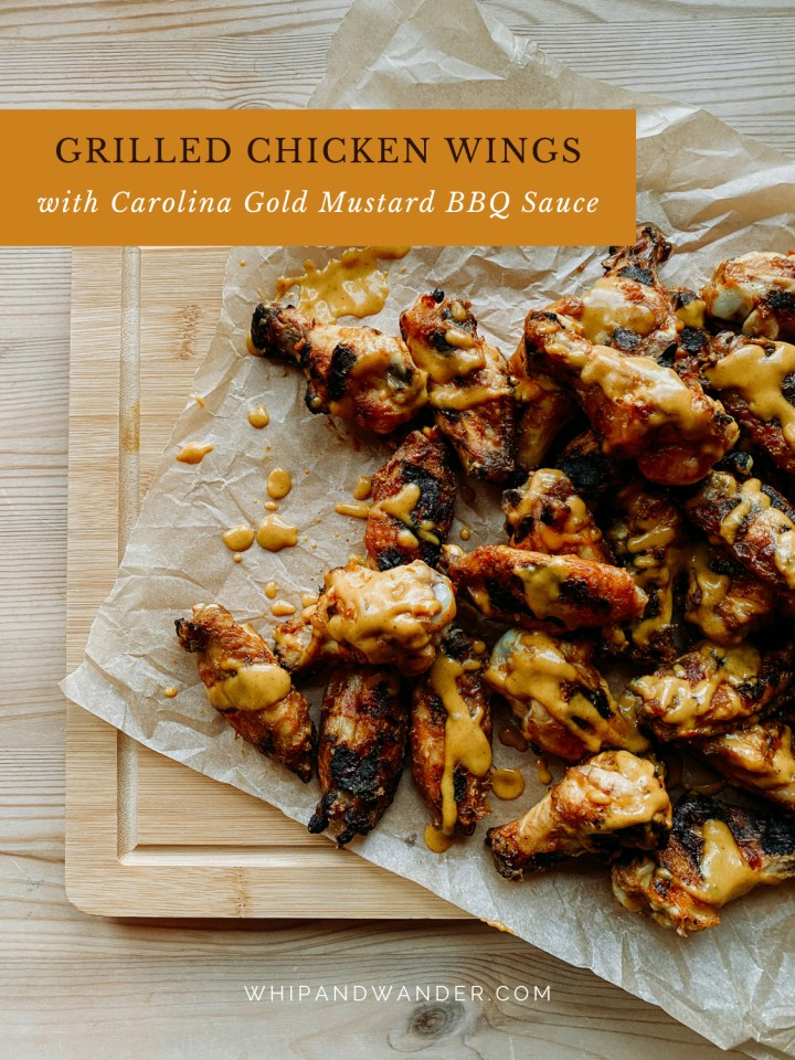 a wooden cutting board with parchment paper, chicken wings, and carolina gold sauce