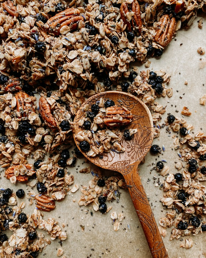 a wooden spoon resting on a baking tray covered in Honey Lavender Blueberry Granola