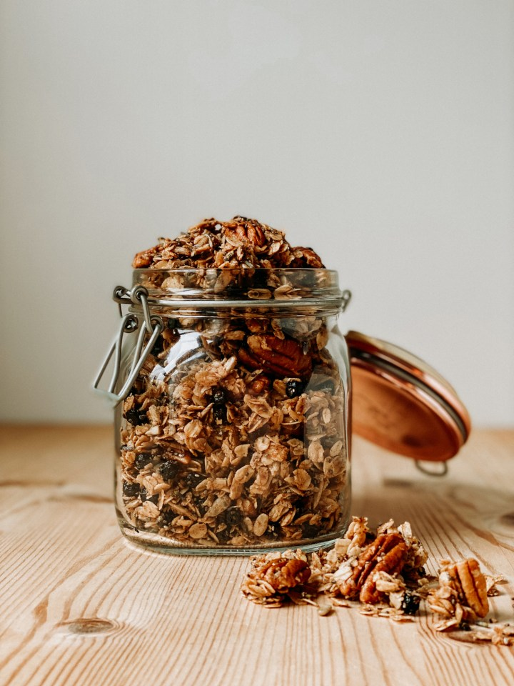 a glass jar with a copper lid filled with Honey Lavender Blueberry Granola resting on a wooden surface