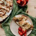 Classic French Crepes on a platter and on a pink plate with strawberries on a green cloth