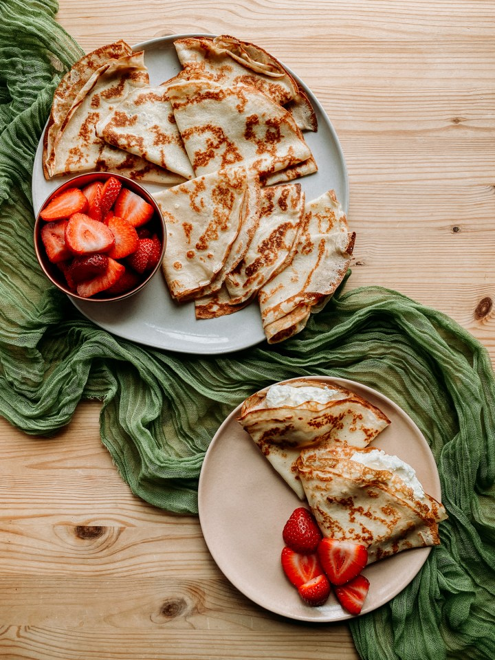 crepes on a large white plate and a smaller pink plate with strawberries on both plates