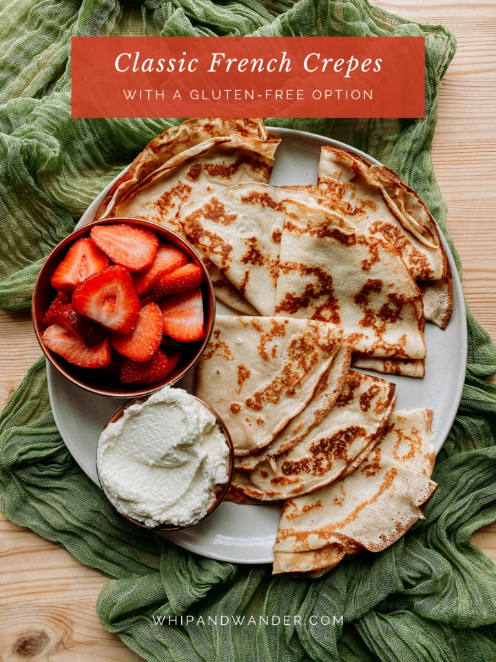 a platter of french crepes, strawberries, and whipped cream on a green fabric cloth