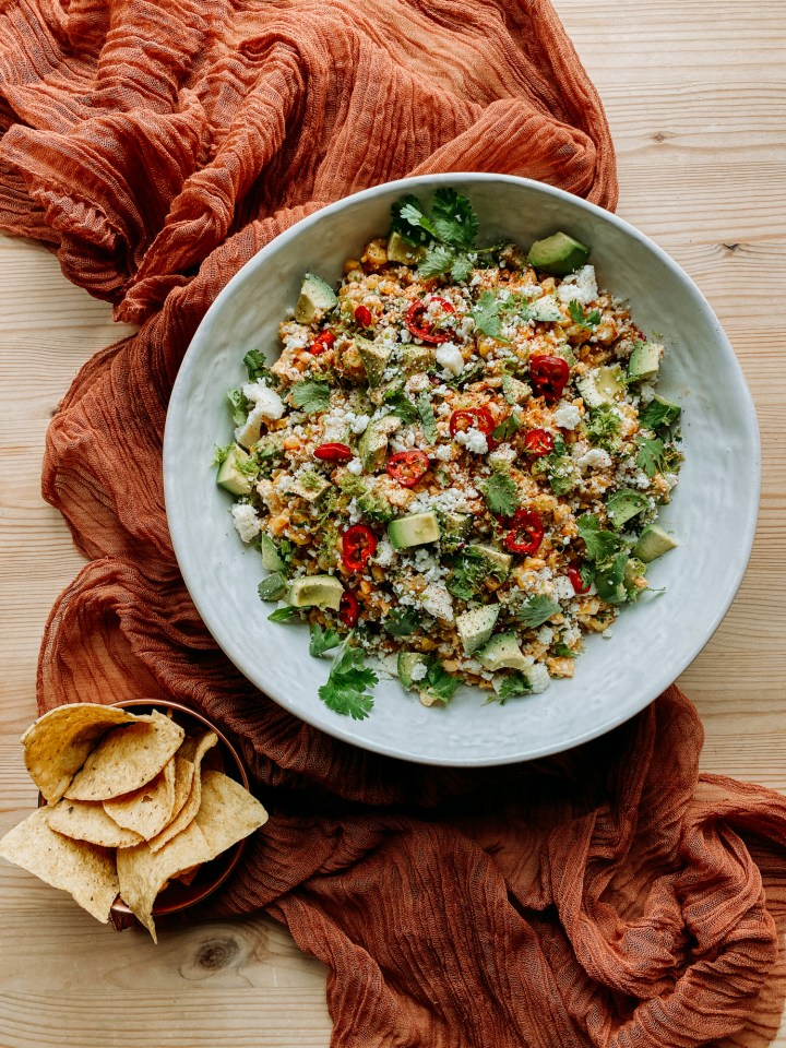 a bowl of tortilla chips resting next to a big white bowl of Grilled Corn Salad with Spicy Honey Lime Dressing