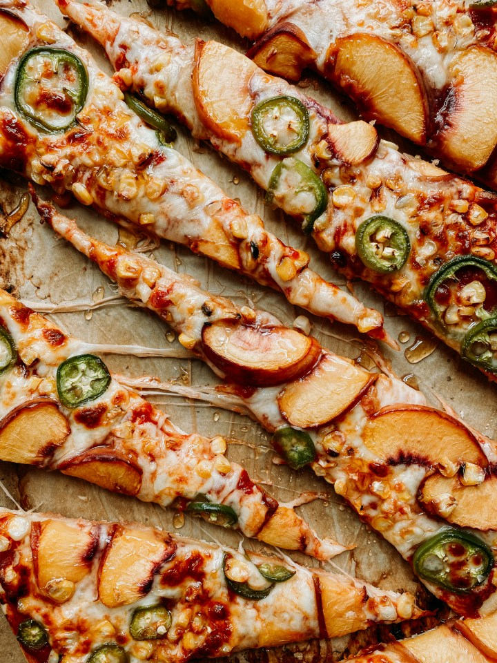 alices of pizza topped with peaches, jalapenos, corn, and honey