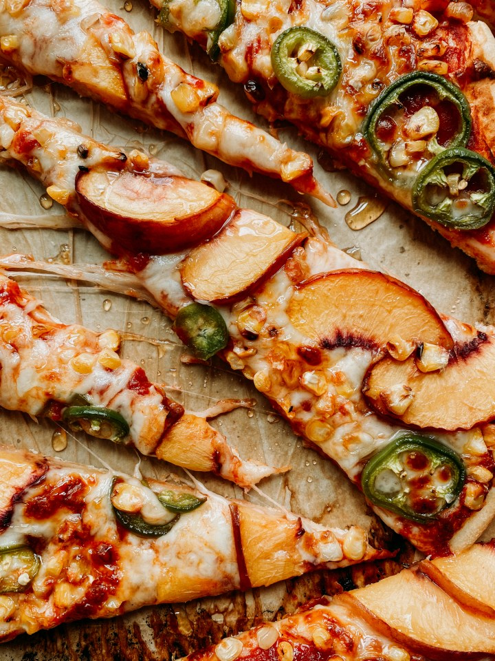 slices of peaches topping pizza slices with corn and jalapenos