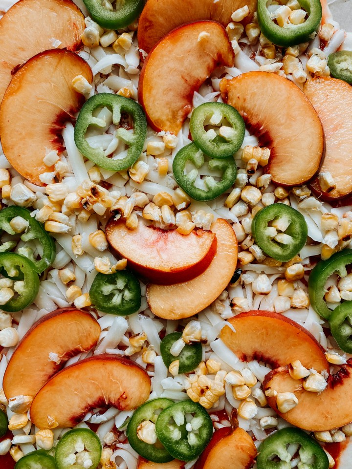 closeup of corn, peaches, and jalapenos on an unbaked pizza