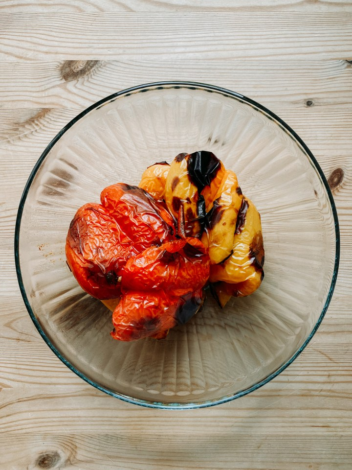 roasted bell peppers in a glass bowl on a wooden tabletop