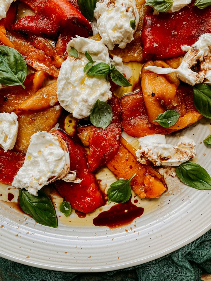 a white dish with peppers, burrata cheese, basil, salt, olive oil, and balsamic vinegar