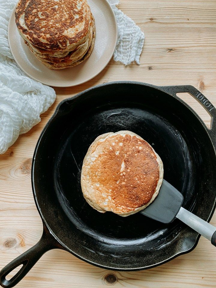 a silicone spatula flipping a pancake in a cast iron pan