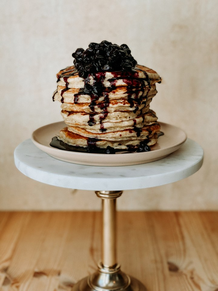 stacks of sourdough discard pancakes with blueberry sauce on a pink plate on a white topped stand