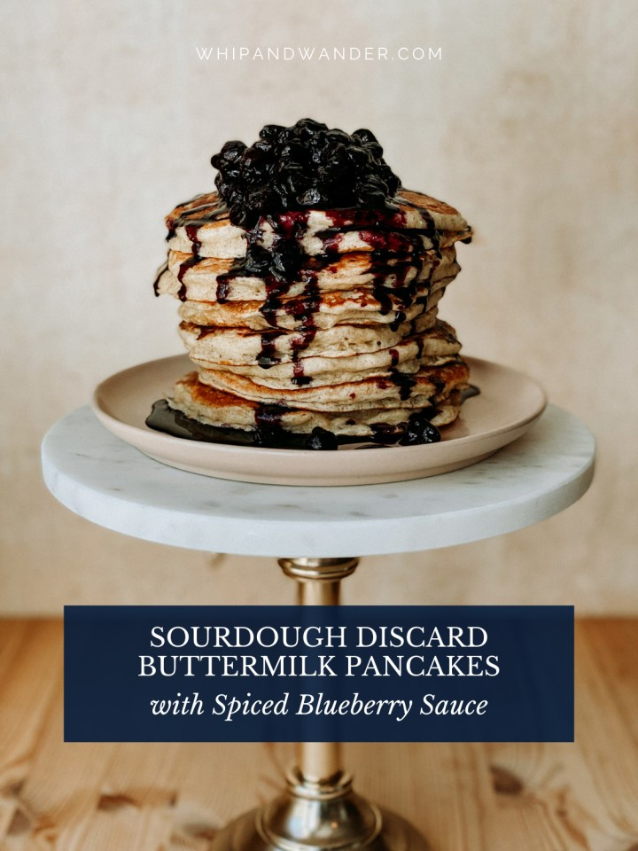 spiced blueberry sauce topped sourdough pancaked on a plate on a white and bronze stand