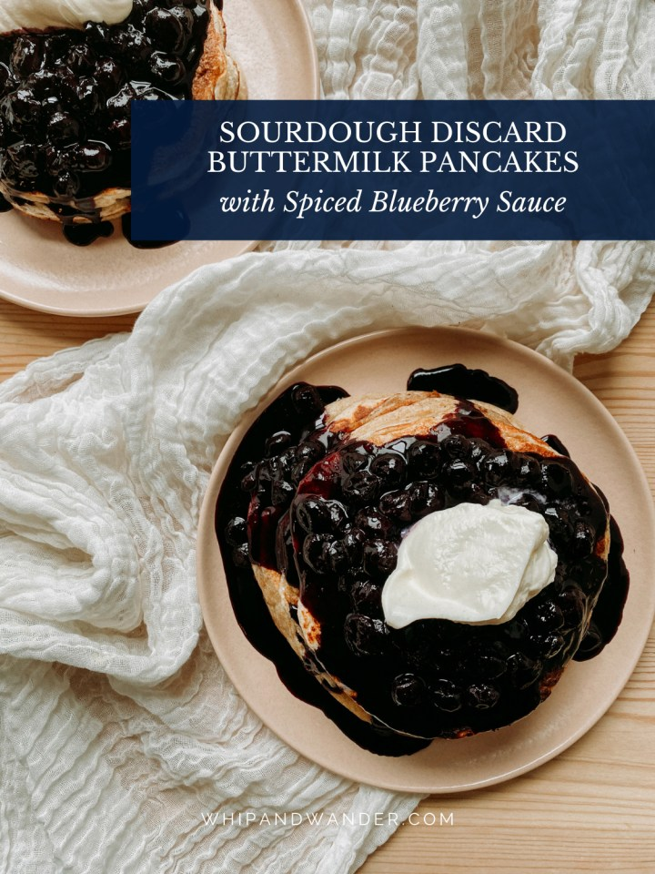 two pink plates with pancakes covered in spiced blueberry sauce and whipped cream
