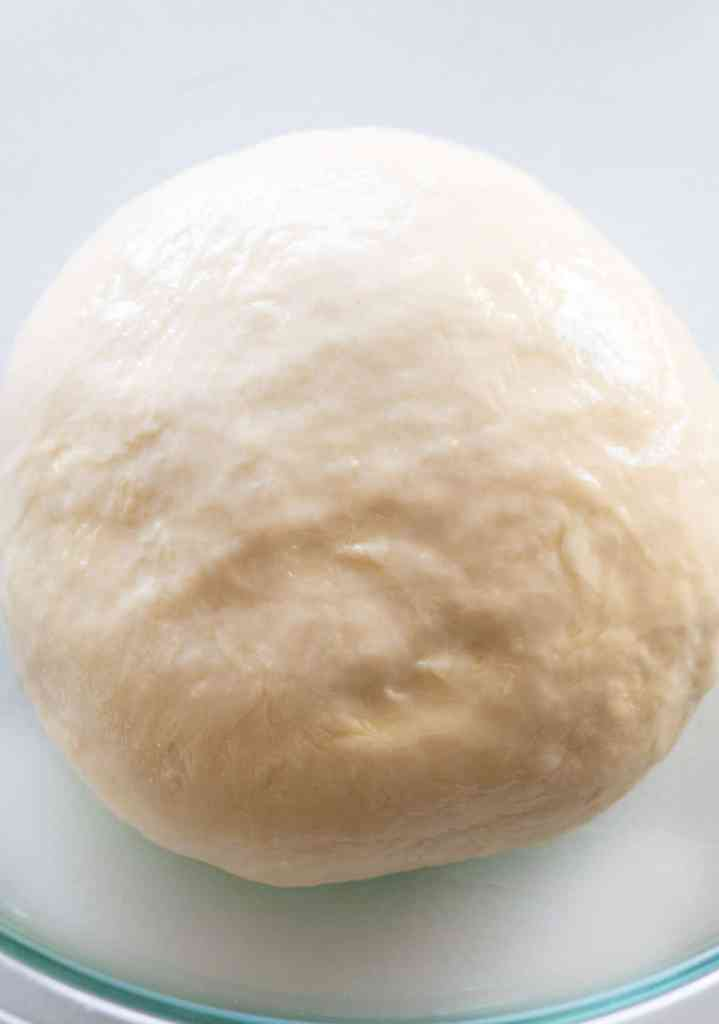 dough ball turned over in a lightly oiled glass bowl