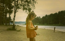 seven year old girl with camera at lake shore in Sweden.