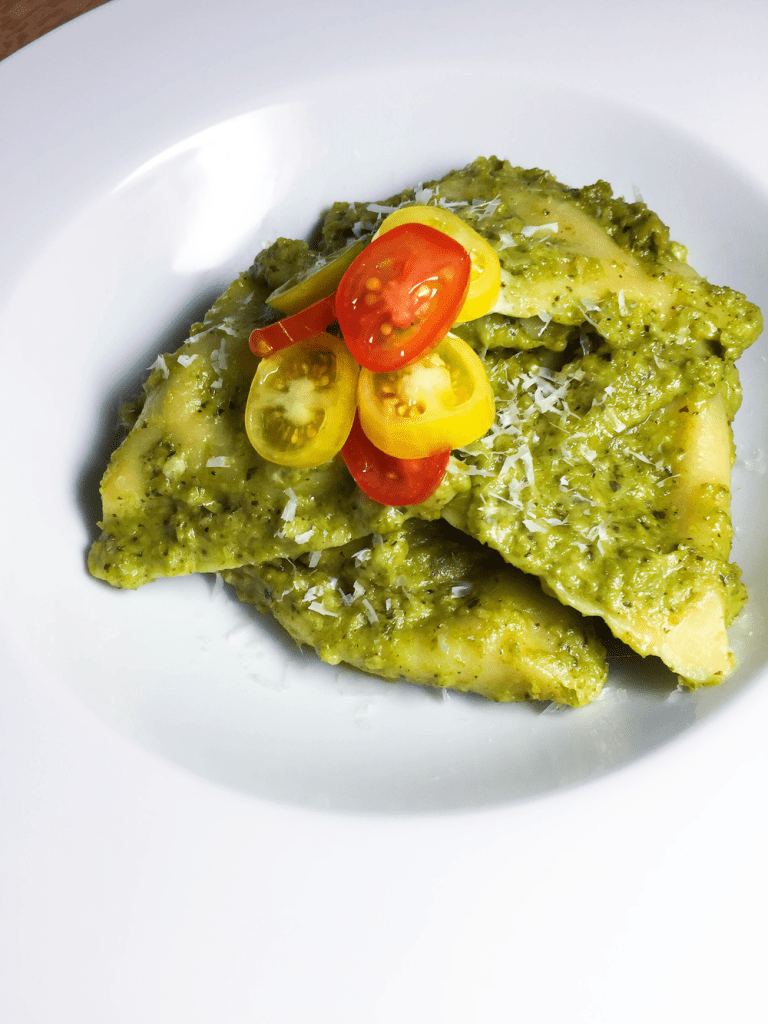 Ravioli in Pea Pesto Cream Sauce in a bowl, topped with red and yellow, sliced cherry tomatoes, close up
